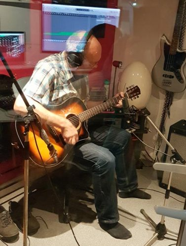 Me playing acoustic guitar in a recording studio.