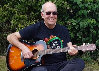 Graham Armfield wearing the Save Our Venues T-shirt and playing a guitar.
